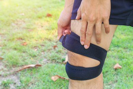 The man wear the Knee Support Brace Patella with sunlight in the park  Knee Pads Hole Sports
