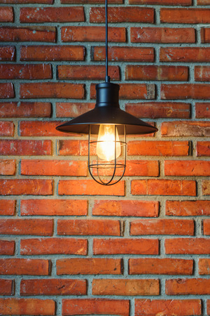 old tungsten Light bulb on Brick background
