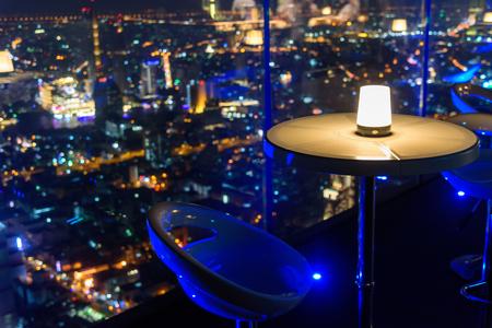 lege stoel met verlichting bij bar op het dak op hoog gebouw