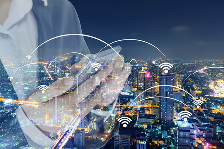 Cityscape of Bangkok with added generic wifi signals and access points and business man use smartphone for connect it Imagens