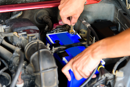 The man turn wrench for Change New Battery of old car