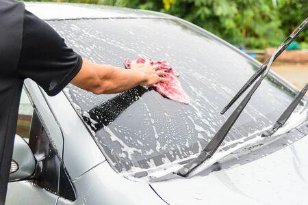 Der Mann wäscht die Windschutzscheibe des Autos Standard-Bild