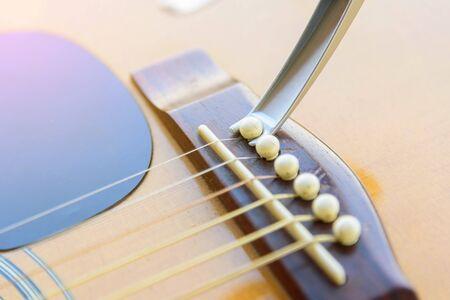 Remove acoustic guitar bridge pin by capo options Stock Photo