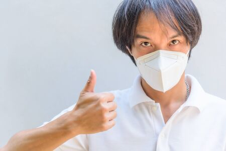 A asian man wear N95 mask and show his hand thum up