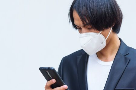A asian man wear N95 mask and use smartphone Stock Photo