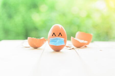 Egg wear the hygienic mask and Broken Egg shell background / safe egg from covid-19 with hygienic mask idea Imagens