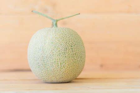 Fresh green melon on wood plate