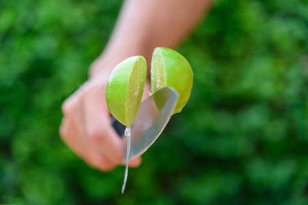 use knife split the fresh green lemon in midair