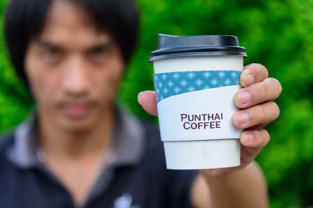Bangkok,Thailand - 6 April, 2021: The man hold the paper cup of Punthai coffee 新聞圖片