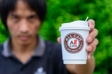 Bangkok,Thailand - 6 April, 2021: The man hold the paper cup of all cafe of hot coffee