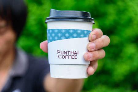 Bangkok,Thailand - 6 April, 2021: The man hold the paper cup of Punthai coffee 版權商用圖片 - 168055157