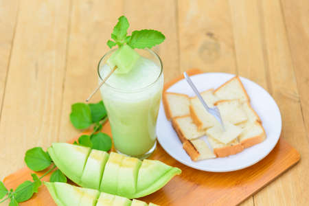Milk melon Smoothie in glass with Roast bread serve on wood plate 版權商用圖片