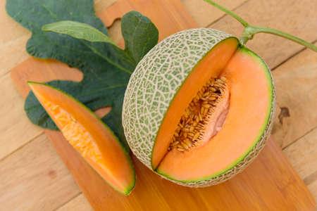 Closeup to split the orange melon on wood plate