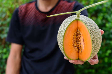 The man show a split the orange melon on wood plate