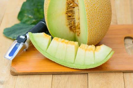 Closeup to Fresh yellow galia melon on wood plate 版權商用圖片