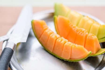Closeup to Fresh Orange melon on wood plate 版權商用圖片