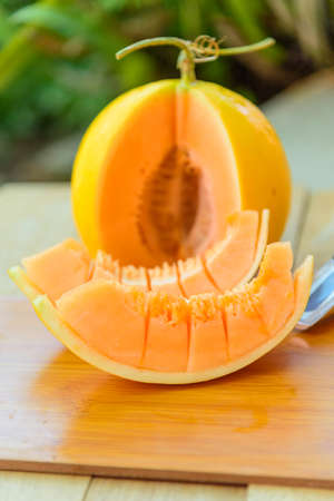 high quality fruits, wooden plate, a lot of piece of fresh orange melon on the plate