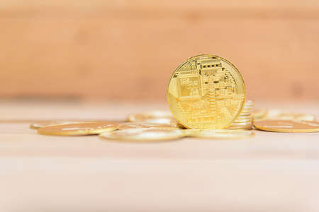 Closeup to Golden Bitcoin cryptocurrency on the wood plate