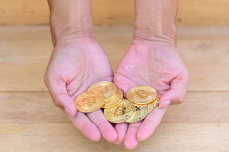 The man show Golden Bitcoin cryptocurrency in his hand