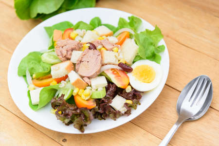 Closeup to tuna salad in the white dish on wood plate