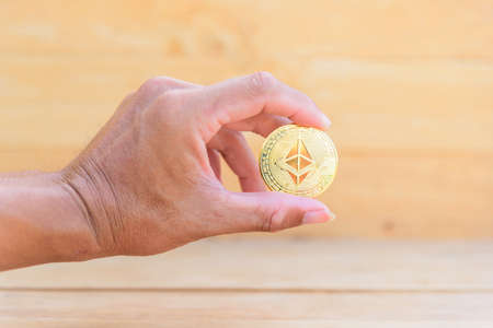 The man show ethereum coin cryptocurrency in his hand