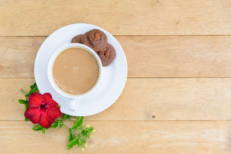Top view of hot coffee with cookie on wood plate