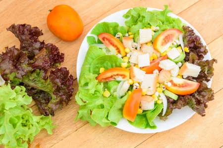 Mixed fresh vegetables salad in white dish on wood plate 版權商用圖片