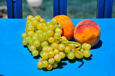 Green grapes and peachs on blue table
