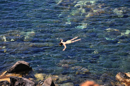 Tourist snorkeling along the rock reef at Red Beach