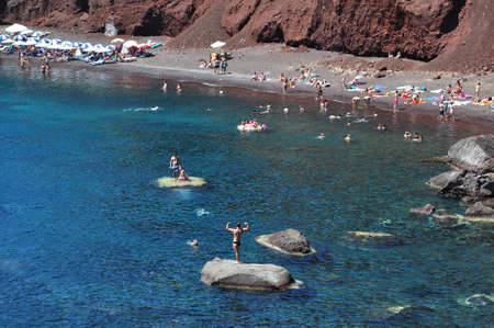Red Beach in Akrotiri, santorini island, Greece. Photo taken at 10th of August 2012 Tourists enjoy time on red beach,  It is located near the village and ancient site of Akrotiri