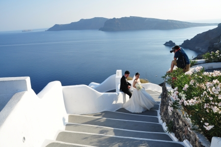 Oia village on Santorini island, Greece - Photo taken at  11th of August 2012 Wedding photographer taking a shot of bride and groom in Oia village on Santorini island
