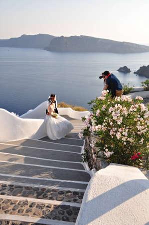 7. Oia village on Santorini island, Greece - Photo taken at  11th of August 2012 Wedding photographer taking a shot of bride and groom in Oia village on Santorini island