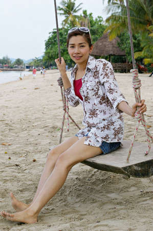 sweet young woman sitting on a swing at the beach, Koh Chang, Thailand