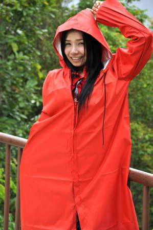 rainwear: Pretty woman in red raincoat on