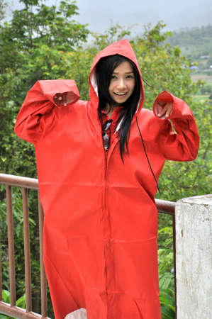 Pretty woman in red raincoat on photo