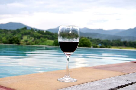 Glass of wine by the pool with bueatiful mountain view