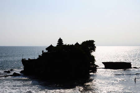 Silhouette of a man walking in the sea at low tide to Tanah Lot temple, Bali, Indonesia photo