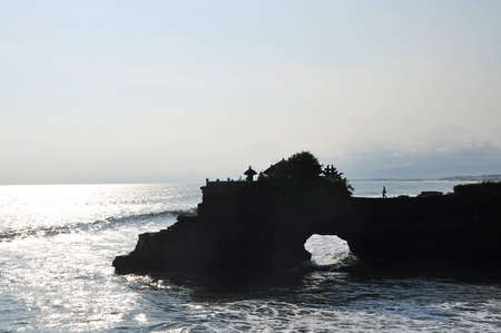 Silhouette of a man walking on natural rock formation to Batu Bolong temple Stock Photo - 17116967