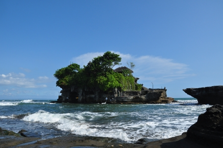 Bali, Indonesia - Tanah Lot temple sits on a large offshore rock which has been shaped continuously over the years by the ocean tide, Bali, Indonesia