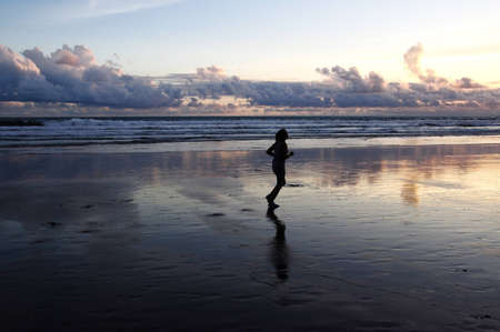 Silhouette of a woman Jogging on Seminyak beach at sunset