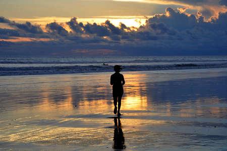 seminyak: Silhouette of a woman Jogging on Seminyak beach at sunset