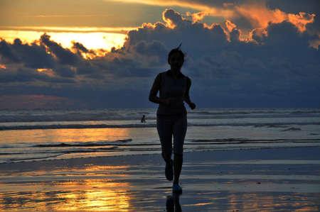 seminyak: woman Jogging  at sunset on Seminyak beach