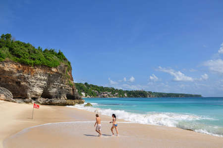 Bali, Indonesia, Photo taken at 26th May 2011 - A couple is walking out of the surf on Dreamland Beach a very beautiful place surrounded by high cliffs