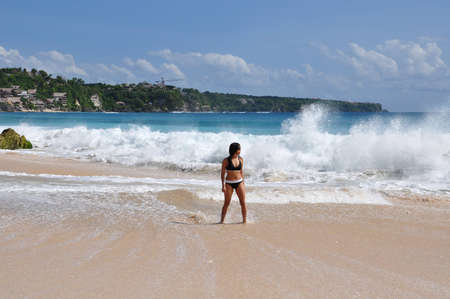 nice accommodations: A female swimmer walking away from a heavy breaking surf