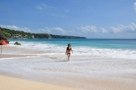 A female swimmer walking on the beach  in the calming surf after the waves retreat