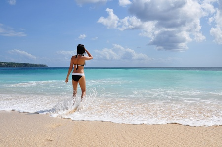 Young woman in a swimsuit standing on the beach by sweeping wave and looking at the horizon