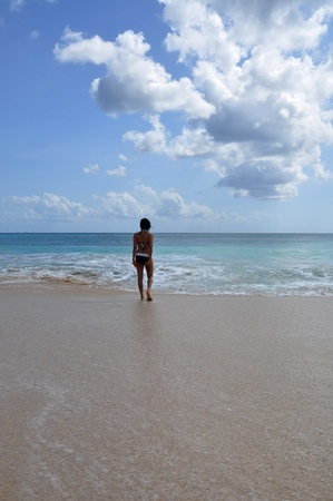A young lady walking into the calm sea after the waves subsided Stock Photo - 17251454
