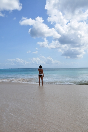 A young lady walking into the calm sea after the waves subsided