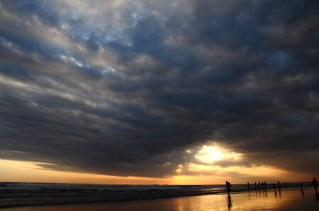 People enjoying last sunrays through low dark clouds just before sunset in Bali Seminyak beach
