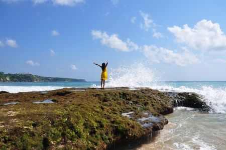 A girl saluting the splashing wave into the mossy sea rock